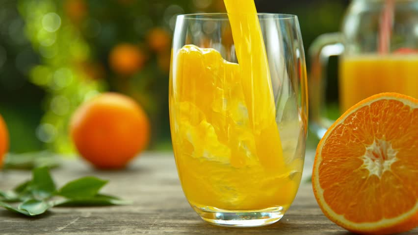 Super Slow Motion Shot of Fresh Orange Juice Being Poured in a Glass at 1000fps.