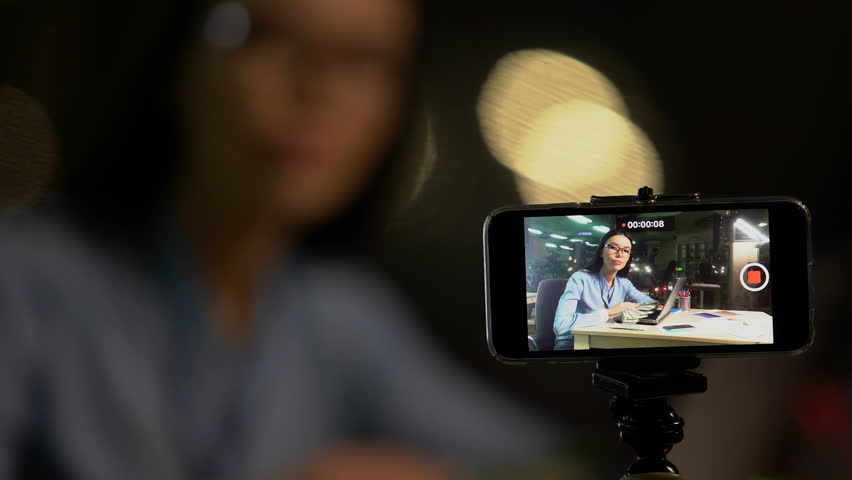 Woman shooting video blog or vlog about making easy money online, advertising