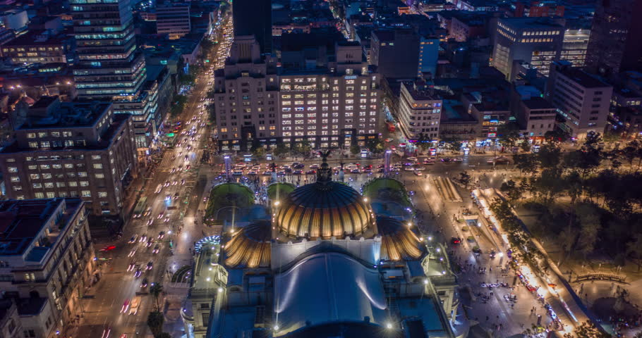 Aerial nocturnal hyperlapse of the Palacio de Bellas Artes, Eje Central street and the Madero pedestrian street at night. Mexico City
