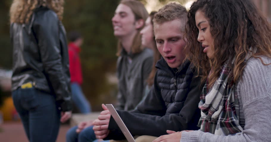 Attractive college students working together and typing on a laptop while sitting outdoors collaborating on a project on a University campus Royalty-Free Stock Footage #1028453177