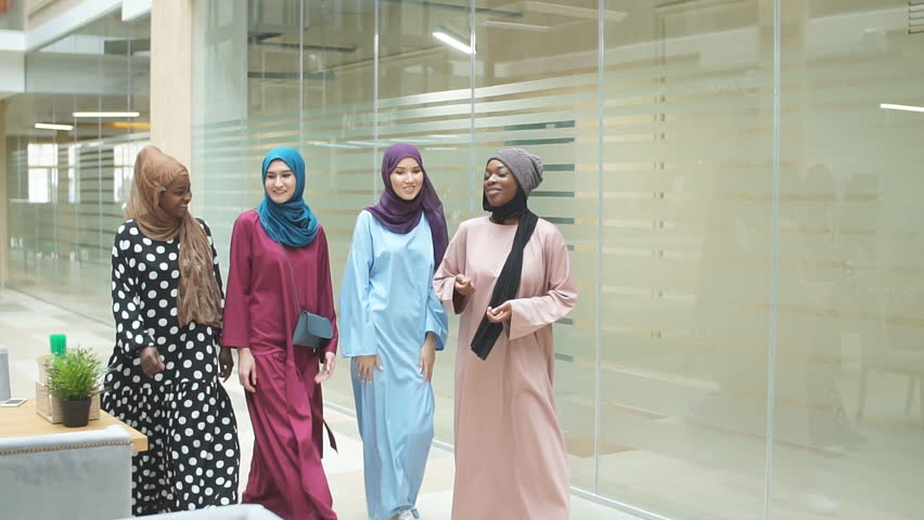 A group of four young muslim multiethnic business women dressed in fashionable tradition dresses chatting and walking together in business centre | Shutterstock HD Video #1028455928
