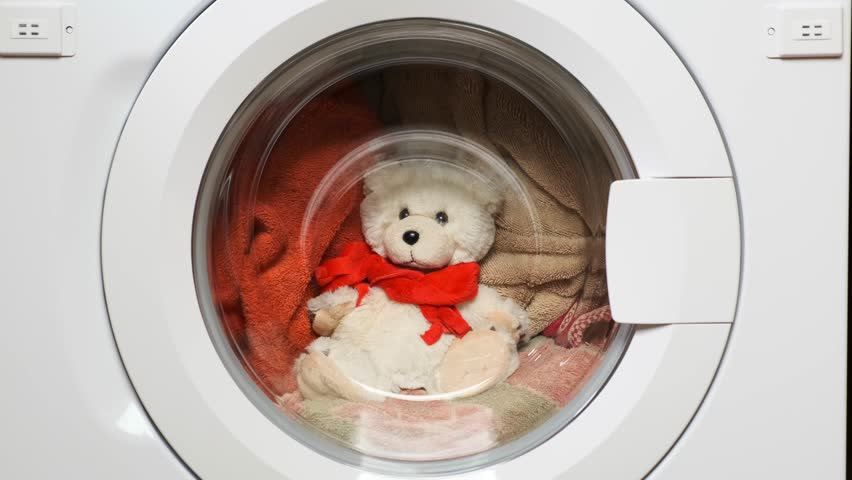 Teddy bear washes in the washing machine. Closeup.