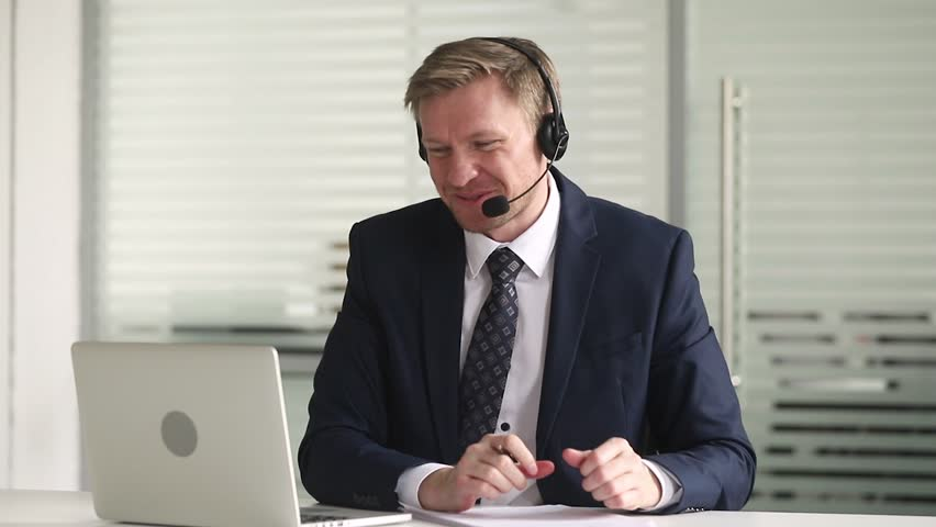 Happy businessman in suit wear headset talking looking at laptop making notes, male customer support manager on conference video call, business man write information consulting client online