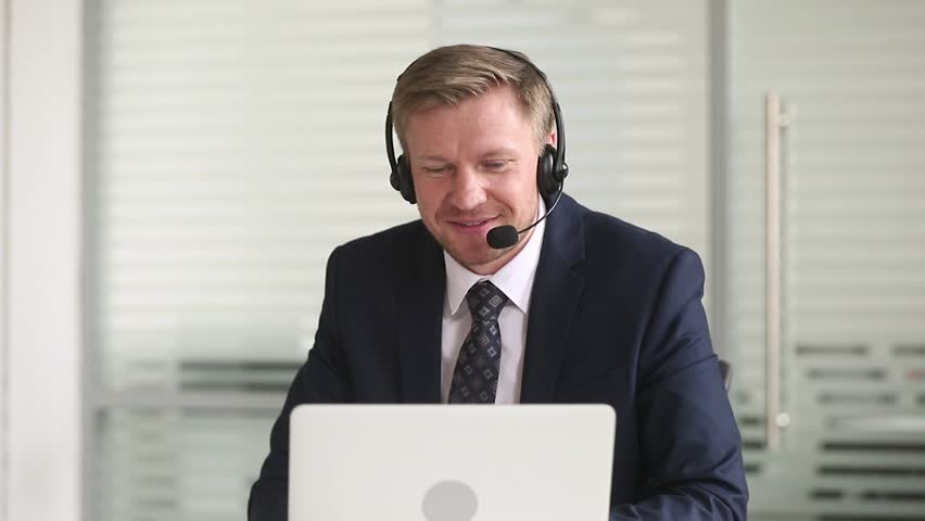Businessman manager in suit talking wearing headset looking at laptop making business conference video call on computer consulting client online in office, customer support service and teleconference