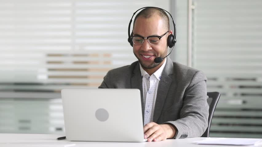 Smiling african american businessman manager talking by video conference call looking at laptop wearing headset, customers service support agent consult client on computer by business teleconference