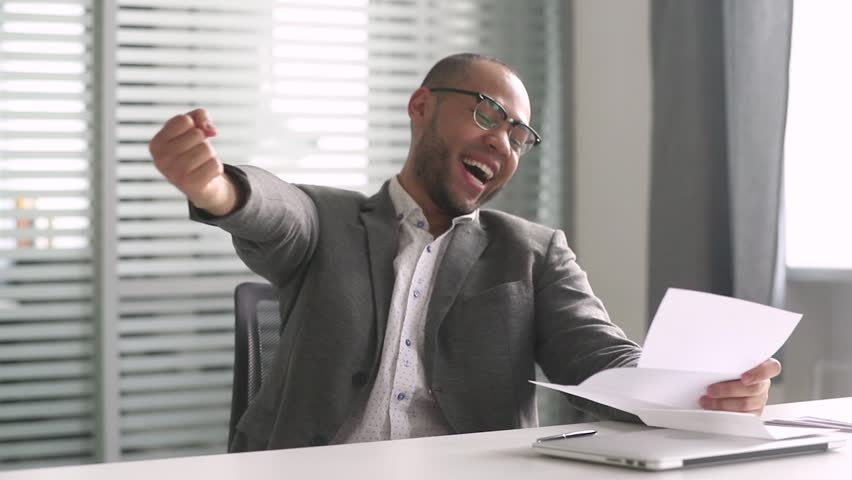 Happy african american businessman winner open envelope read mail letter excited by good news got new job hired promoted, overjoyed by loan approval, receiving bill salary celebrating taxes refund   Shutterstock HD Video #1028495291
