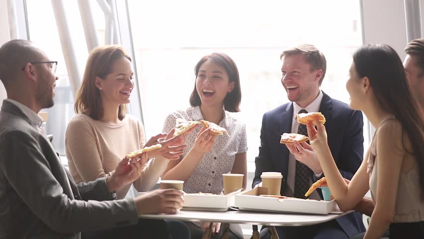 Happy multicultural business team people talking laughing eating pizza together in office, cheerful workers staff group chatting sharing lunch food dinner meal enjoying having fun at work break | Shutterstock HD Video #1028495312