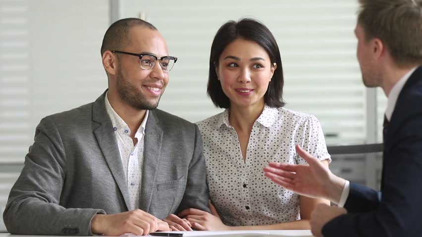 Happy mixed ethnicity couple clients customers signing bank loan contract paper handshake manager make agreement insurance investment mortgage deal shake hand of agent salesman insurer at meeting Royalty-Free Stock Footage #1028495363