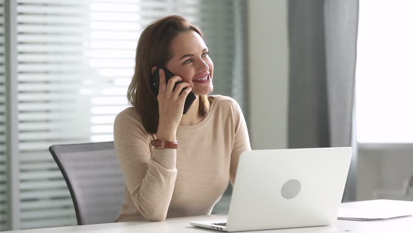 Smiling millennial business woman talking on the phone making business call consulting client or chatting with friend, happy young female secretary having mobile conversation in office at workplace