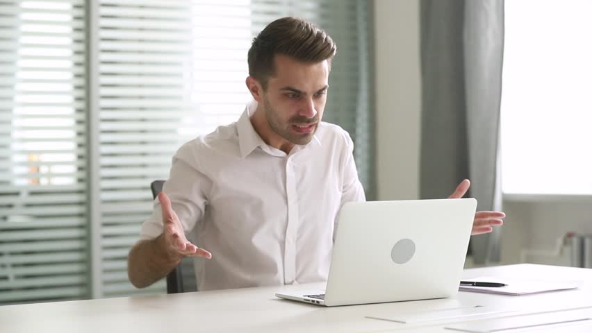 Angry stressed mad business man looking at stuck laptop using pc having problem with computer in office, frustrated outraged worker annoyed with online failure, application error or system virus