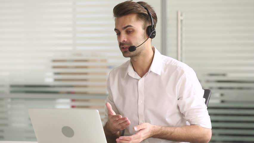 Male customer service support agent telemarketer wearing headset looking at laptop make business conference internet video call, businessman consult client in online chat in office by teleconference