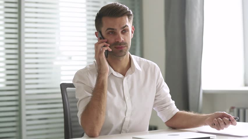 Young businessman talking on phone consulting client support customer sit at work desk, male manager entrepreneur speak by mobile smartphone having conversation on cell making business call in office