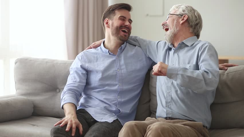 Happy generations old father laughing embracing young son giving fist bump sit on sofa at home, friendly senior dad hug adult man talking joking having fun enjoy time together and good relationships | Shutterstock HD Video #1028497853