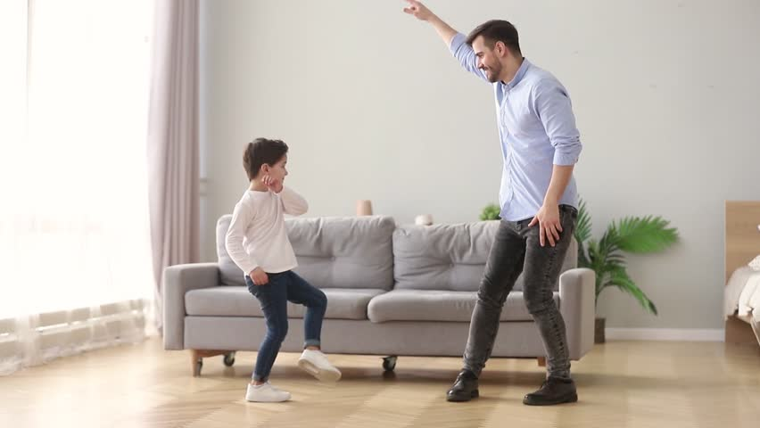 Happy young dad and cute little kid son dancing having fun in living room together, funny active small boy laughing imitating father moving to music, daddy child playing at home on weekend leisure | Shutterstock HD Video #1028497871