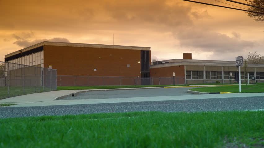 Sunset evening school exterior establishing 4k video shot. DX elementary high education building street view lock down. Beautiful orange sky and clouds overhead.