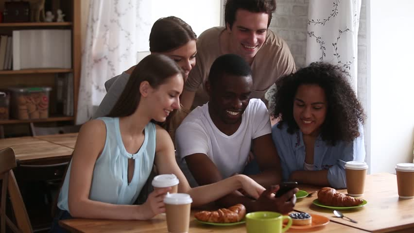 Multi racial students gather in cafe have fun together african ethnicity guy holds smart phone make video call wave hands greeting friends, generation of modern tech users communication online concept #1028517194
