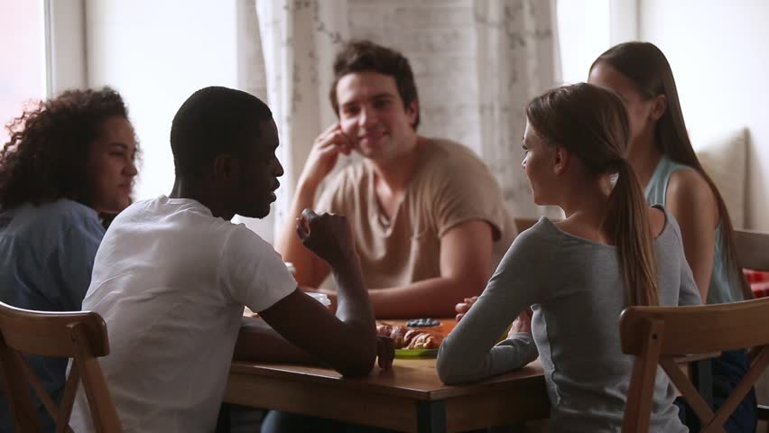 Rear view african guy sitting around the table with multi-ethnic friends telling story hang out with diverse millennial students enjoy free time with guys and girls drink coffee chatting in cafeteria