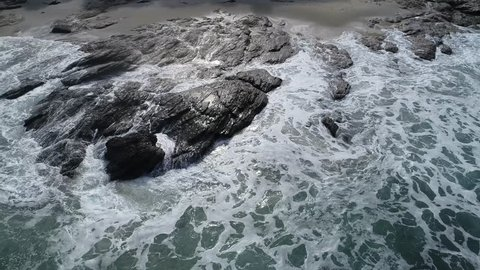 Aerial view waves break on on rock coast with spray and foam before storm in Brighton Beach, New Zealand. Sea waves on the beautiful beach aerial view drone 4k shot.