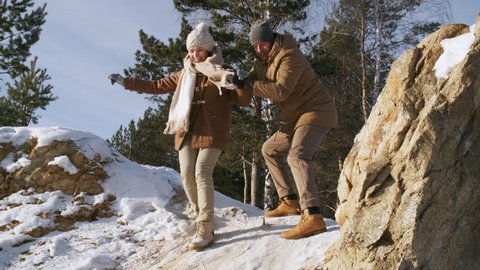 Full low-angle shot of happy middle-aged couple, dressed in jackets and woolly hats, during winter walk in pine forest, with man helping woman descend down small stony slope and cheering