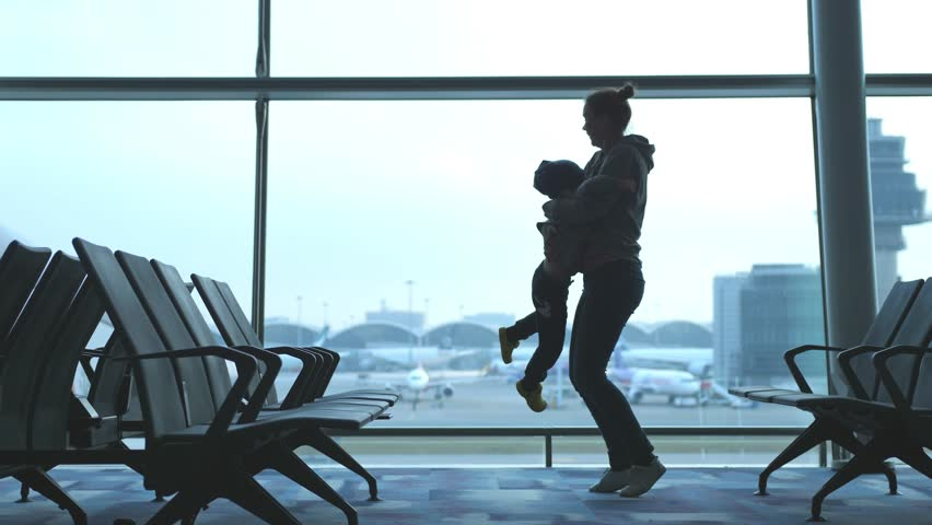 Mother embracing son and spinning around loving family waiting for flight. slow motion. 3840x2160. 4k