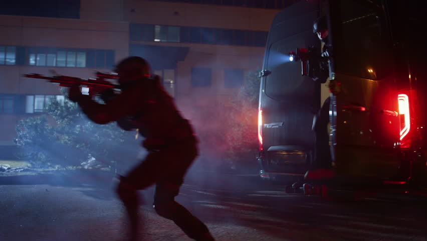 Masked Team of Armed SWAT Police Officers Exit a Black Van Parked Outside of an Office Building. Soldiers with Rifles and Flashlights Run on a Street Filled with Smoke.
