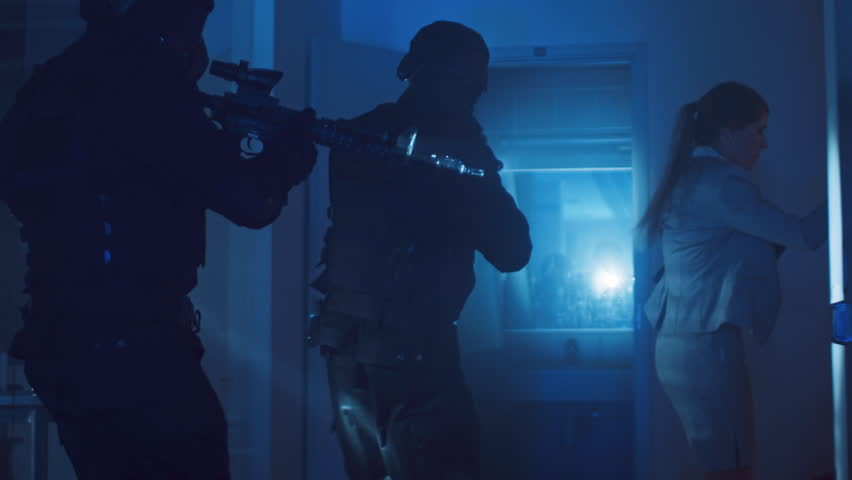 Masked Squad of Armed SWAT Police Officers Rescue a Female Hostage in a Dark Seized Office Building with Desks and Computers. Soldiers with Rifles and Flashlights Move Forwards and Cover Surroundings. | Shutterstock HD Video #1028544218