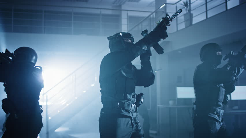 Masked Squad of Armed SWAT Police Officers Stand in Dark Seized Office Building with Desks and Computers. Soldiers with Rifles and Flashlights Surveil and Cover Surroundings. | Shutterstock HD Video #1028544353