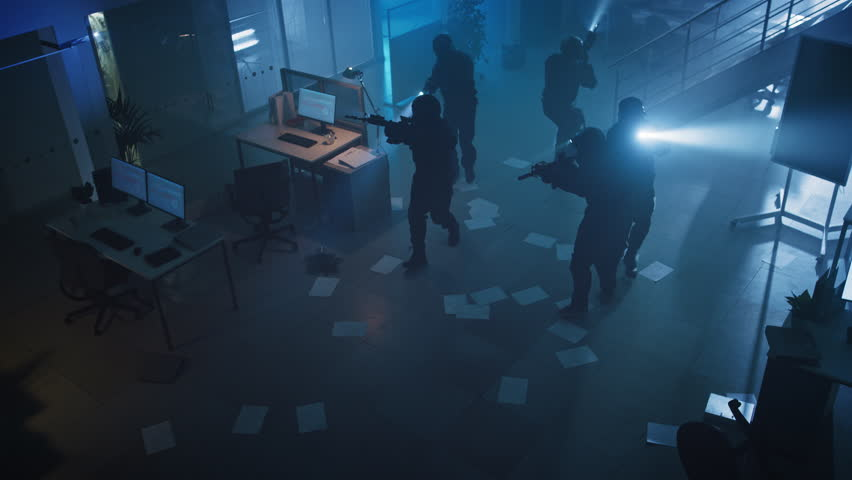 Masked Squad of Armed SWAT Police Officers Storm a Dark Seized Office Building with Desks and Computers. Soldiers with Rifles and Flashlights Move Forwards and Cover Surroundings. Above-view Camera. | Shutterstock HD Video #1028544425
