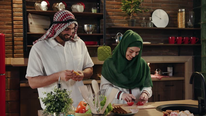 Young joyful smiling Arabic couple together preparing food in a modern kitchen and actively talking. Having fun, couple goals, happy together. Cooking process, home routine. Modern family