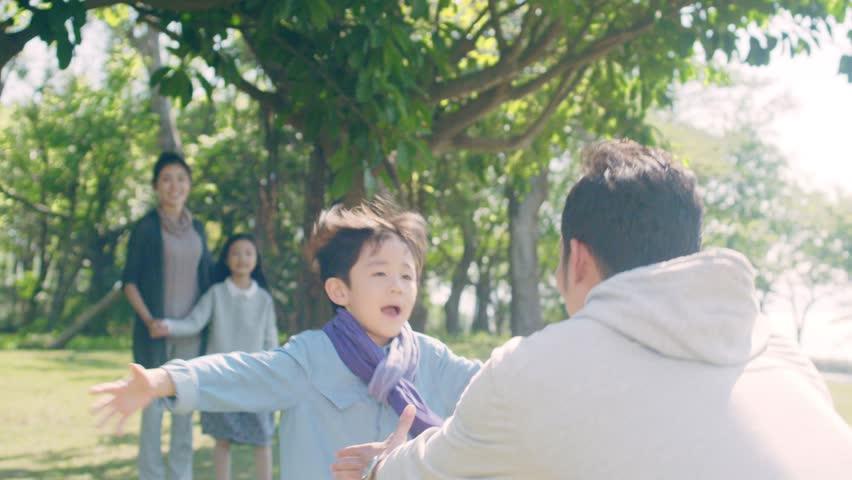 Lovely asian boy running toward father in park