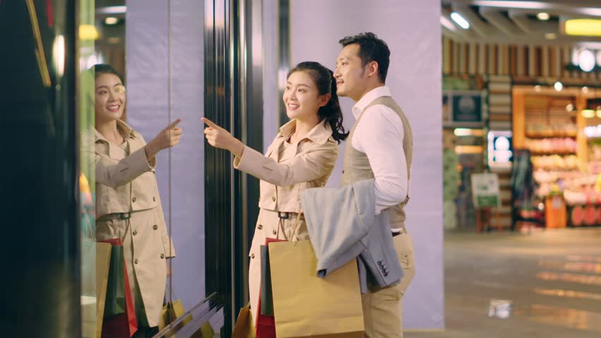 Happy asian couple shoppers walking in shopping mall