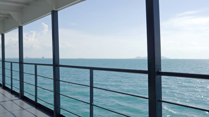 Big Ferry Boat for Passengers With Fence Sailing On Calm Turquoise Water ith View on Distant Island and Horizon #1028586920