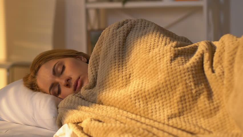 Woman turning under blanket, hardly awaking in morning, sleeping schedule