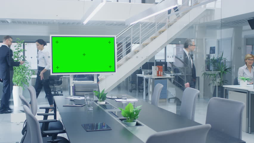 In the Corporate Office Meeting Room Stands Green Mock-up Screen TV or Interactive Digital Whiteboard in Horizontal Mode. In the Background Big Bright Busy Office with Businesspeople Working Royalty-Free Stock Footage #1028612102