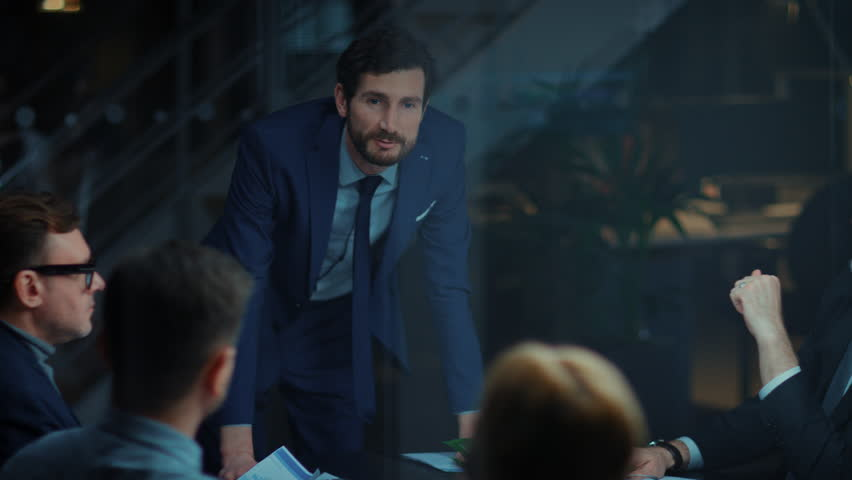Corporate Meeting Room: Confident and Handsom Executive Director Decisively Leans on a Conference Table and Delivers Report to a Board of Executives about Company's Record Breaking Revenue