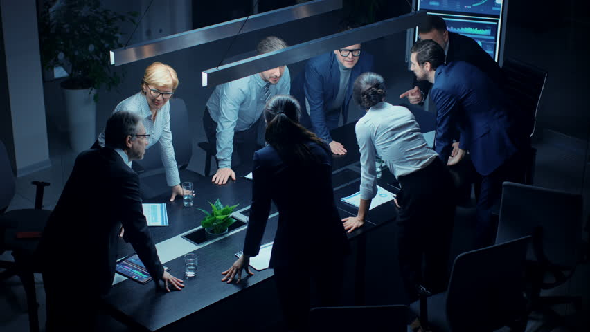In the Dark Corporate Meeting Room Diverse Group of Executives, Business Associates and Investors Lean on a Conference Table During Emotional Discussion, Planning and Strategizing. High Angle Camera | Shutterstock HD Video #1028612156