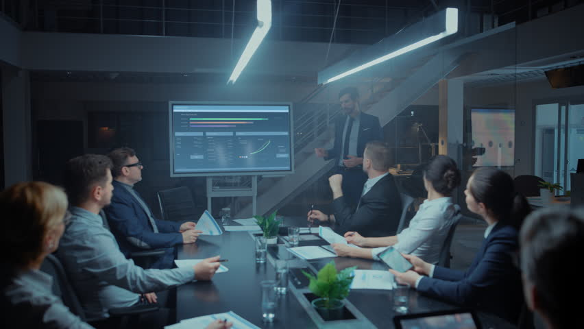 In the Corporate Meeting Room: Male Executive Talks and Uses Digital Interactive Whiteboard for Presentation to a Board of Directors, Investors. Screen Shows Growth Data. Late at Night Office