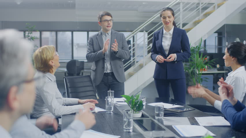In the Corporate Office Meeting Room: Two Young and Ambitions Start-up Creators Give a Speech to a Group of Venture Capital Investors, Businesspeople Cheer and Applaud in Successful Agreement