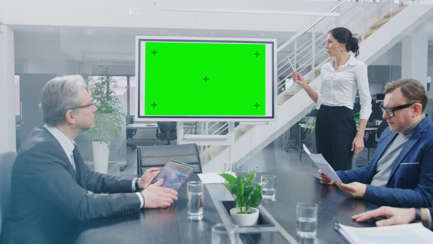 In the Corporate Meeting Room: Female Speaker Uses Digital Chroma Key Interactive Whiteboard for Presentation to a Board of Executives, Lawyers, Investors. Green Mock-up Screen in Horizontal Mode Royalty-Free Stock Footage #1028612327