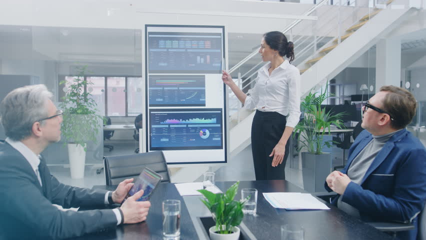 In the Corporate Meeting Room: Female Analyst Uses Digital Interactive Whiteboard for Presentation to a Board of Executives, Lawyers, Investors. Screen Shows Company Growth Data with Animated Graphs