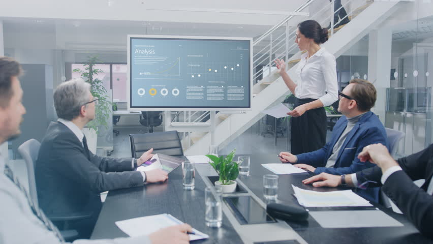 In the Corporate Meeting Room: Female Analyst Uses Digital Interactive Whiteboard for Presentation to a Board of Executives, Lawyers, Investors they Applaud. Screen Shows Company Growth Data Royalty-Free Stock Footage #1028612339