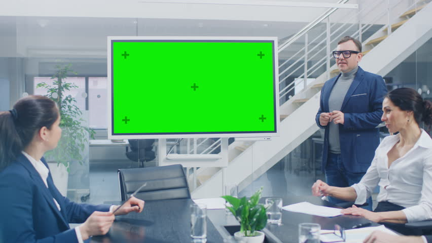 In the Corporate Meeting Room: Creative Director Uses Digital Chroma Key Interactive Whiteboard for Presentation to a Board of Executives, Lawyers, Investors. Green Mock-up Screen in Horizontal Mode Royalty-Free Stock Footage #1028612342