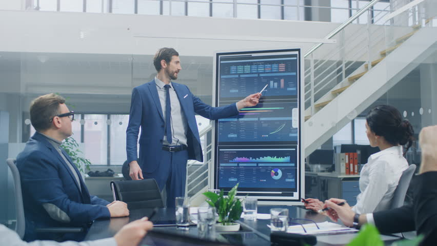 In the Corporate Meeting Room: Ambitious Executive Uses Digital Interactive Whiteboard for Presentation to a Board of Directors, Lawyers, Investors. Screen Shows Company Growth Data with Graphs Royalty-Free Stock Footage #1028612363