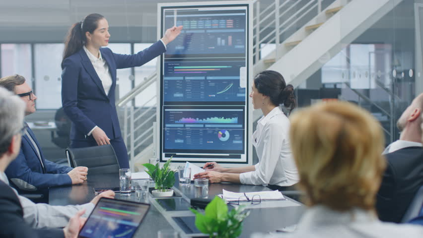 In the Corporate Meeting Room: Young and Talented Female CEO Uses Digital Interactive Whiteboard for Presentation and Delivers Powerful Speech to a Board of Executives, Lawyers, Investors   Shutterstock HD Video #1028612372