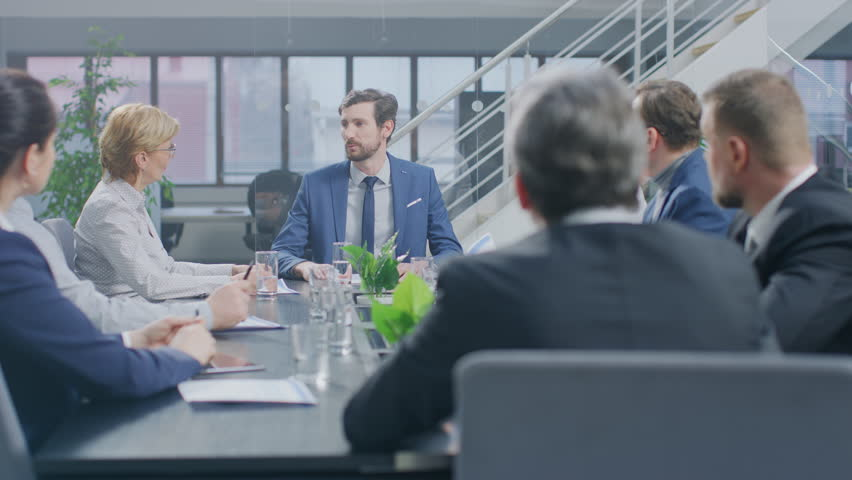 In the Corporate Meeting Room Close-up on the Hands of Businesspeople, Signing Contracts, Using Smartphones and Digital Tablet Computers, Gesticulating. People Sitting at Conference Table | Shutterstock HD Video #1028612423