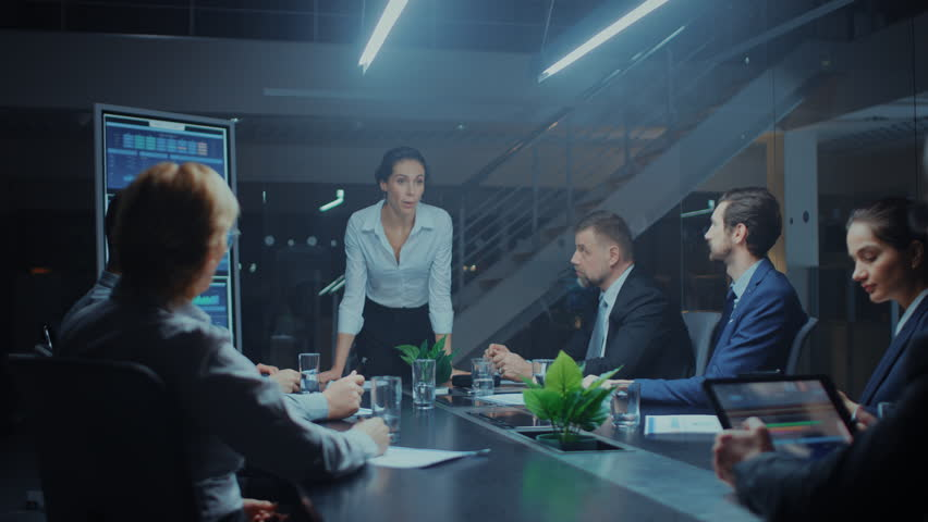 Late at Night in the Meeting Room: Confident Female Executive Director Stands in the Head of the Conference Table Leans on it and Delivers Ground Breaking Speech to a Group of Businesspeople | Shutterstock HD Video #1028612447
