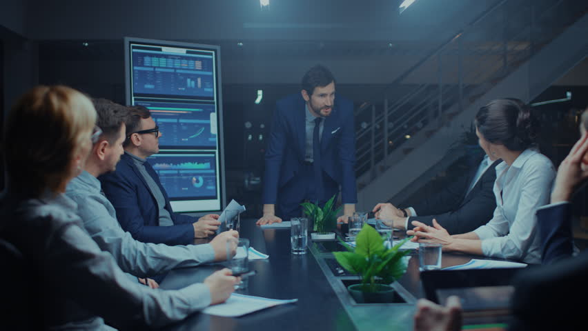 Late at Night in the Meeting Room: Handsome Executive Director Stands in the Head of the Conference Table Leans on it and Delivers Eloquent Speech to a Group of Businesspeople and Investors. Royalty-Free Stock Footage #1028612462