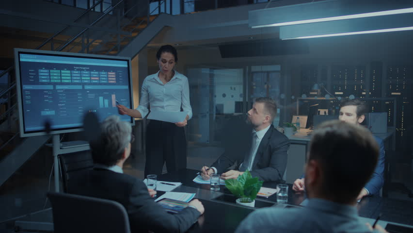 In the Corporate Meeting Room: Female Executive Talks and Uses Digital Interactive Whiteboard for Presentation to a Board of Directors, Investors. Screen Shows Growth Data. Late at Night Office | Shutterstock HD Video #1028612498