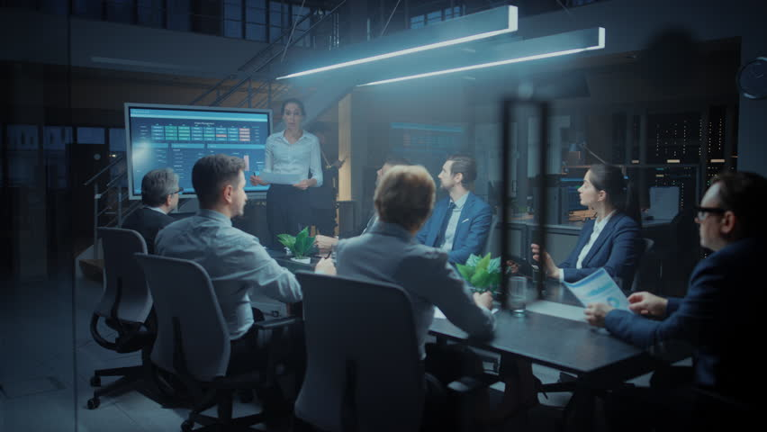 In the Corporate Meeting Room: Female Executive Talks and Uses Digital Interactive Whiteboard for Presentation to a Board of Directors, Investors. Screen Shows Growth Data. Late at Night Office | Shutterstock HD Video #1028612504