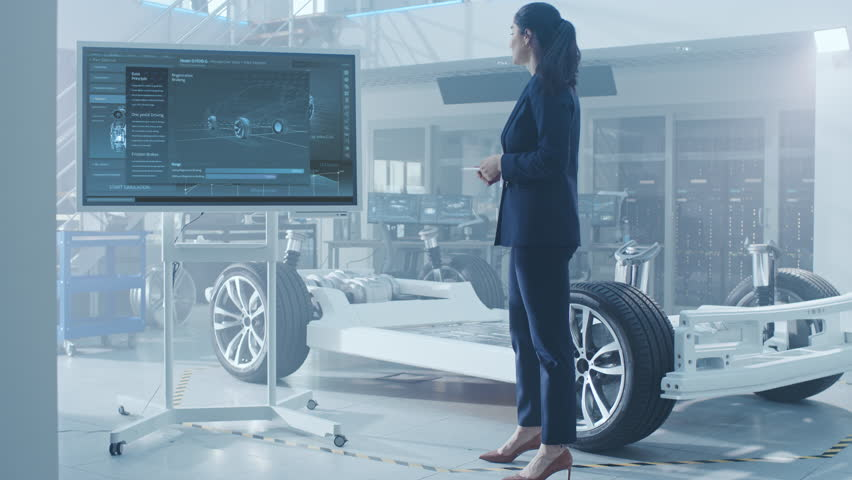 Male and Female Design Engineers are Working and Discussing Something on a Interactive Whiteboard Next to an Electric Car Chassis Prototype. In High Tech Laboratory Facility with Vehicle Frame.